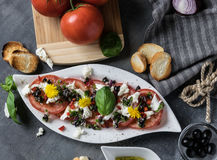 Fresh salad of tomatoes and mozzarella. Recipe with olive oil with red onion, olives and basil Royalty Free Stock Photos