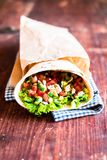 Fresh salad tortilla wraps with cucumbers, tomatoes, onion, prawns on rustic background, selective focus. Picnic food. Healthy and stock photo