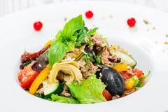 Fresh salad with tuna, arugula, artichokes, codfish, olives, basil, sun dried tomatoes, cherry tomatoes, cucumber, cauliflower Royalty Free Stock Photos
