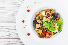 Fresh salad with tuna, arugula, artichokes, codfish, olives, basil, sun dried tomatoes, cherry tomatoes on wooden background Royalty Free Stock Photos