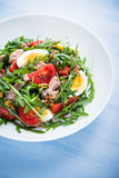Fresh salad with tuna, tomatoes, eggs, arugula and mustard on blue wooden background close up Stock Photo