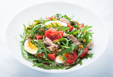 Fresh salad with tuna, tomatoes, eggs, arugula and mustard on white textured background close up Stock Photo
