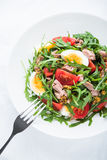 Fresh salad with tuna, tomatoes, eggs, arugula and mustard on white textured background top view Royalty Free Stock Images