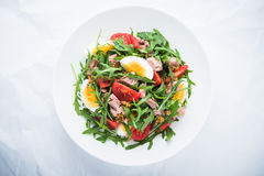 Fresh salad with tuna, tomatoes, eggs, arugula and mustard on white textured background top view Royalty Free Stock Image