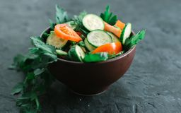 Fresh salad with vegetables on a black matte background. The concept of a healthy diet Stock Image