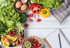 Fresh salad vegetables and fruit with notebook and pencil Stock Photography