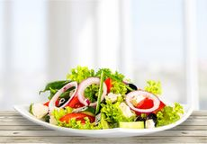 Greek salad with fresh vegetables on wooden table stock photo