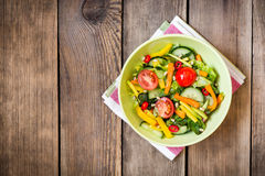 Fresh salad with vegetables, greens and pine nuts on wooden background Stock Photography