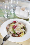 Fresh salad with vegetables and meat on the served table Stock Photography