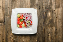 Fresh salad and vegetables in white plate on wooden background top view Royalty Free Stock Image