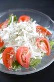 Fresh salad with whitebait simply scalded. Close up shot of frash salad with whitebait simply scalded on black background royalty free stock photos
