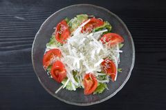 Fresh salad with whitebait simply scalded. Close up shot of frash salad with whitebait simply scalded on black background royalty free stock photography