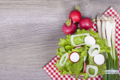 Fresh salad on a wooden background. Fresh lettuce, onion and radish on wooden background. With empty space for your text. View from above Royalty Free Stock Images