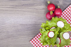 Fresh salad on a wooden background. Fresh lettuce and radish on wooden background. With empty space for your text. View from above Royalty Free Stock Photography