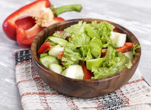 Fresh salad. Salad in a wooden bowl, fresh vegetables with apple Royalty Free Stock Images