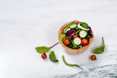Fresh salad in wooden bowl on white marble stone Royalty Free Stock Image