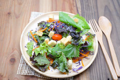 Fresh salad in wooden plate on wood table Royalty Free Stock Photo