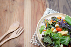 Fresh salad in wooden plate on wood table Royalty Free Stock Image