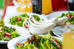 Fresh salads on the plates and sause. On the dinner table Royalty Free Stock Photo