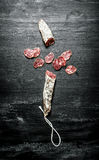 Fresh salami . On black chalkboard. Stock Photo