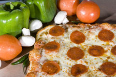 Fresh salami pizza. A closeup of a freshly baked salami pizza with capsicums, tomatoes and mushrooms placed next to it royalty free stock photos