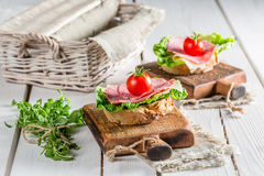 Fresh salami on sandwich. On old wooden table royalty free stock photo