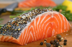 Fresh salmon. Steak sprinkle coarse ground pepper and salt Royalty Free Stock Image