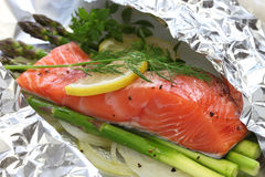 Fresh salmon with asparagus in foil. Paper, ready for cooking stock image