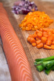 Fresh salmon with chopped vegetables on a board Stock Photo