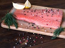 Fresh salmon fillet with aromatic herbs and spices. Fresh salmon fillet with lemon, salt, tomato, herbs on wooden background. Close up. Top view. Concept of Royalty Free Stock Photography