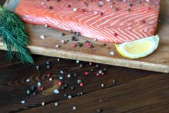 Fresh salmon fillet with aromatic herbs and spices. Fresh salmon fillet with lemon, salt, herbs on wooden background. Close up. Top view. Concept of healthy diet Royalty Free Stock Photography