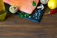 Fresh salmon fillet with aromatic herbs, spices, mushrooms, oil,. Lemon and cutting board of dark stone on wooden background. Top view. Closeup. With free space Royalty Free Stock Photo
