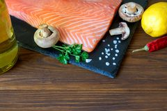 Fresh salmon fillet with aromatic herbs, spices, mushrooms, oil,. Lemon and cutting board of dark stone on wooden background. Top view. Closeup. With free space Stock Photos