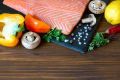 Fresh salmon fillet with aromatic herbs, spices, mushrooms, pepp. Er, lemon and cutting board of dark stone on wooden background. Top view. Closeup. With free Royalty Free Stock Images