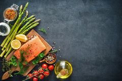 Fresh salmon fillet with aromatic herbs, spices and vegetables. Balanced diet or cooking concept Stock Image