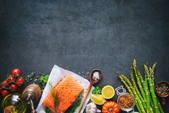 Fresh salmon fillet with aromatic herbs, spices and vegetables. Balanced diet or cooking concept Royalty Free Stock Photography