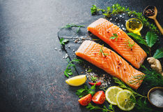 Fresh salmon fillet with aromatic herbs, spices and vegetables. Balanced diet or cooking concept Royalty Free Stock Photos