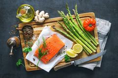 Fresh salmon fillet with aromatic herbs, spices and vegetables. Balanced diet or cooking concept Royalty Free Stock Photo