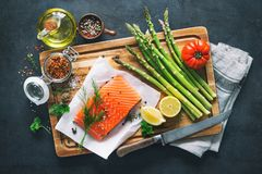 Fresh salmon fillet with aromatic herbs, spices and vegetables. Balanced diet or cooking concept Stock Photo