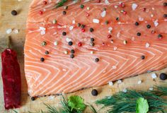 Fresh salmon fillet with aromatic herbs, spices and vegetables. Fresh salmon fillet with salt, herbs on wooden background. Close up. Top view. Concept of healthy Stock Photos