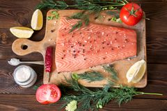 Fresh salmon fillet with aromatic herbs, spices and vegetables. Fresh salmon fillet with lemon, salt, tomat, herbs on wooden background. Cose up. Top view Stock Photo
