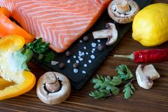 Fresh salmon fillet with aromatic herbs, spices and vegetables. Fresh salmon fillet with aromatic herbs, spices, mushrooms, pepper, lemon and cutting board of Royalty Free Stock Photos