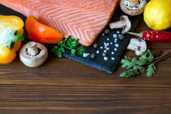 Fresh salmon fillet with aromatic herbs, spices and vegetables. Fresh salmon fillet with aromatic herbs, spices, mushrooms, pepper, lemon and cutting board of Royalty Free Stock Photo