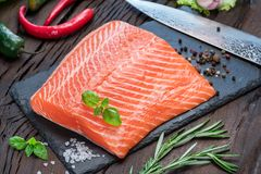 Fresh salmon fillet on black cutting board. Fresh salmon fillet on black cutting board with herbs and spices Royalty Free Stock Photos