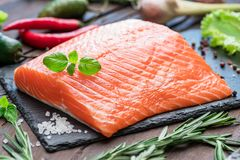 Fresh salmon fillet on black cutting board with herbs and spices.  Royalty Free Stock Photography