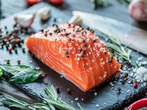 Fresh salmon fillet on black cutting board with herbs and spices.  Stock Photo