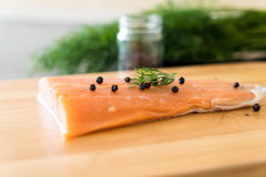Fresh Salmon Fillet on board. With black peppers Royalty Free Stock Photo
