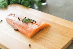 Fresh Salmon Fillet on board. With black peppers Royalty Free Stock Photos