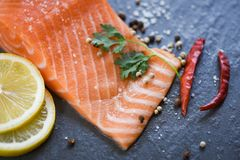 Fresh salmon fillet on dark background Close up of raw salmon fish seafood with lemon herbs and spices royalty free stock photos