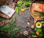 Fresh salmon fillet with ingredients for tasty cooking on rustic wooden background, top view, frame. Stock Photography